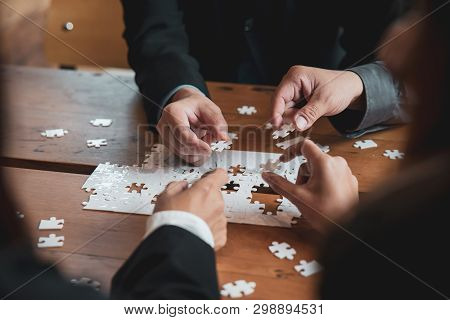 Group Of Business People Holding Piece Of Jigsaw Puzzle To Solution Problem On Wooden Table.professi