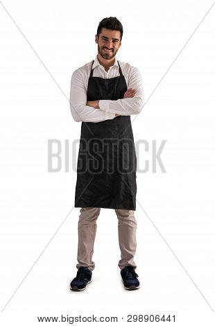 Full Length Shot Of Young Chef Or Waiter Posing, Wearing Black Apron And White Shirt Isolated On Whi