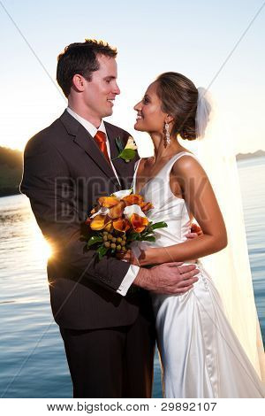Groom Holding Bride At Sunset With Sunburst