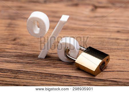 Percentage Sign Locked With Keypad Lock On Wooden Desk