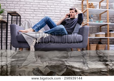 Flooded Floor From Water Leakage In Front Of Man Sitting On Sofa Calling To Plumber
