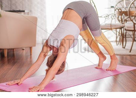 Beautiful Woman Is Practicing Yoga, Doing Adho Mukha Svanasana Pose, Standing In Downward Facing Dog