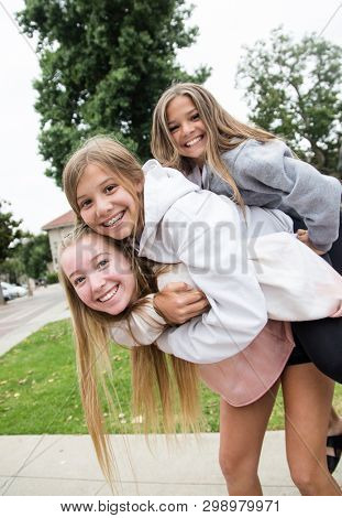 Group of three teen girls having fun and playing together outdoors. Cute teenage girls giving each other a piggy back