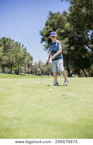 A young boy putting a golf ball on the green while playing golf. Vertical photo of a child learning the game of golf