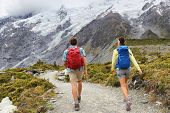 New Zealand travel tramping hikers walking on trail of Hooker Valley Track in New Zealand Aoraki/Mt Cook. Couple tourists hiking in mountains on popular tourist destination. Kiwi trampers with bags. poster
