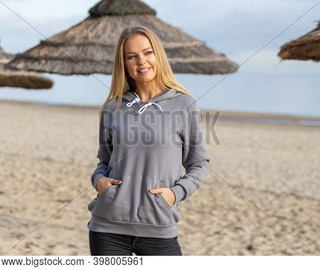 Smiling blond woman wears grey hoodie on beach in summer or autumn. She stands in front of camera with hands in pockets. Copy space on cloth for mockup.
