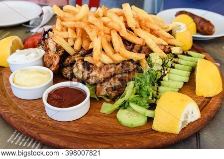 Traditional Greek Chicken And Pork Souvlaki Served With Fries In Greek Tavern.