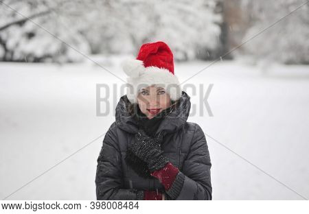 young woman with santa claus hat in a snowy park
