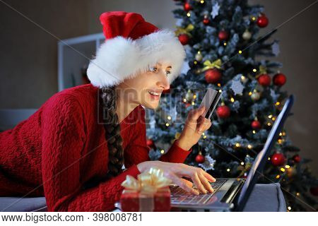 The Girl Is Preparing For Christmas And Orders Gifts For Her Family Via The Internet Using A Credit