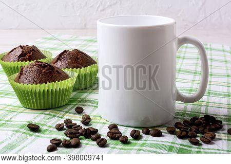 White Mug Mockup With Chocolate Muffins On Green Checkered Napkin.  Empty Mug Mock Up For Design Pre