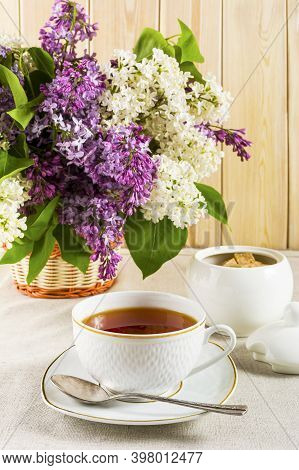 Cup Of Tea And Branch Of Lilac Flower On Linen Tablecloth. Spring Tea Time Concept. Breakfast Tea Cu