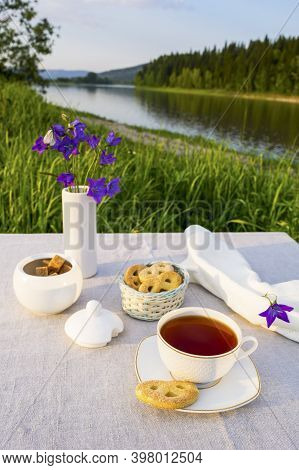 Evening Tea Summer Sunset River View. Cup Of Tea And Cookies In Small Wicker Basket With Blue Bell F
