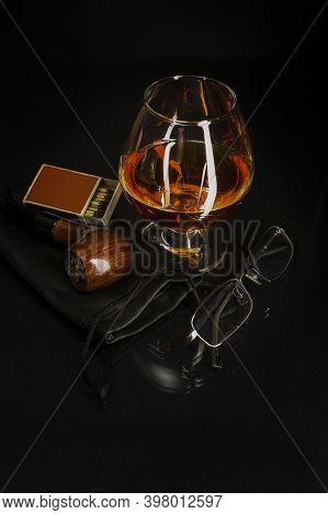 Glass Of Cognac And Smoking Pipe. Cognac Glass. Brandy Glassful. Cognac France. Smoking Pipe And Sco