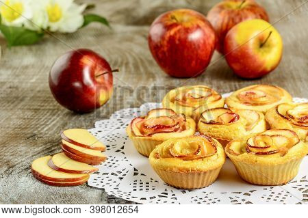 In Shaped Roses Apple Muffins On Wooden Background. Sweet Apple Dessert Pie. Homemade Apple Rose Pas