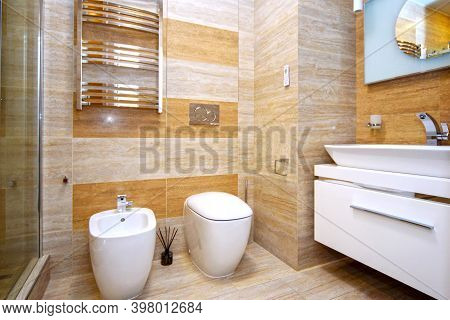 Clean And White Toilet And Bidet With Gold-plated Faucet In The Beige Bathroom.