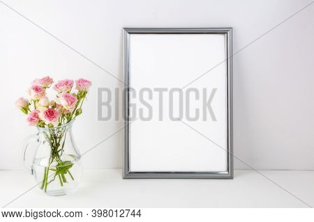 Silver Frame Mockup With Pink Roses In Glass. Portrait Or Poster White Frame Mockup. Empty White Fra
