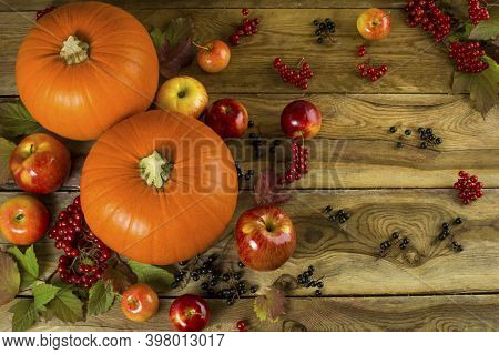 Fall, Ripe Pumpkins, Apples, Berries And Leaves On Wooden Background. Selective Focus. The Toning