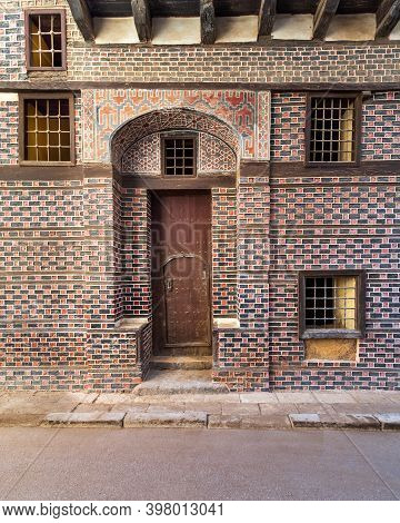Facade Of Old Building With Black And Red Bricks Wall With White Seam, Grunge Wooden Decorated Arche