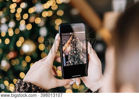 Young Woman Takes Pictures Of Christmas Tree On Smartphone. Close-up. High Quality Photo