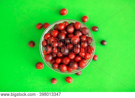 Fresh Red Cranberries In A Glass Bowl On Green Background