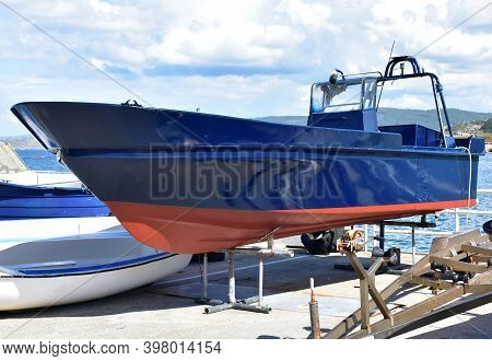 Blue And Red Motor Boat In A Harbor. Rias Baixas, Galicia, Spain.