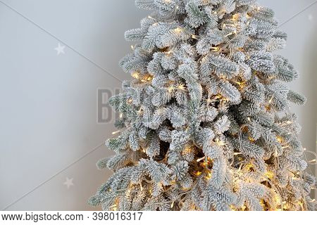 Fir Tree Branches With Glowing Yellow Christmas Light. Close-up Christmas Snowy Tree In Living Room.