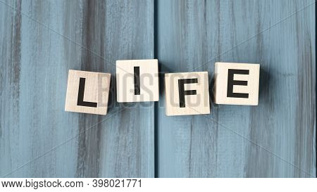 Woman Holding A Wooden Cube Whit The Inscription: Life, With Pink Tulips On The White Background. Sa