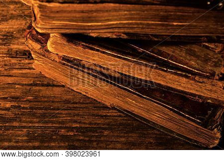 Stack Of Old Worn Leather-bound Book On Textured Wood Background In Candlelight. Selective Focus. Lo