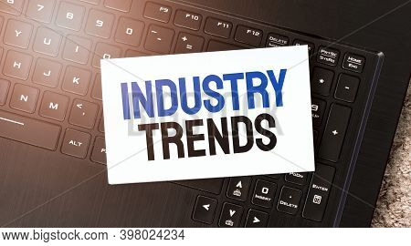 White Paper Sheet With Text Industry Trends On The Black Laptop