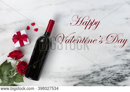 Happy Valentines Day With Lovely Rose Flowers And Red Wine Bottle Plus Giftbox On Natural Marble Sto