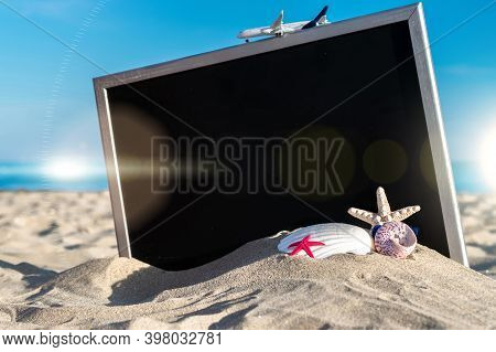 Sea Background. Globe, Seashell, Airplane And Starfish Near Black Desk On Sea Beach In Sunny Day. Ex
