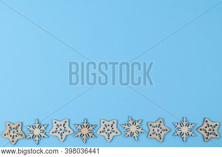 A Texture Formed By Small Wooden Christmas Icons On A  Blue Background