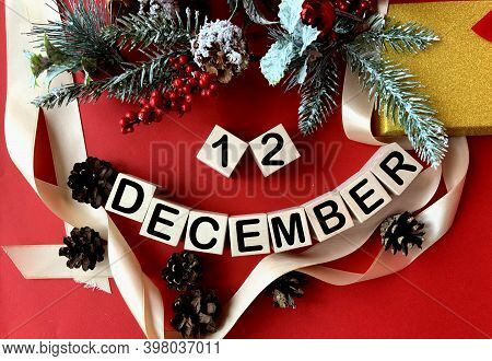 December 12 On Wooden Cubes.near Fir Branches, Cones, Ribbon, Gift Box On A Red Background.winter.ca