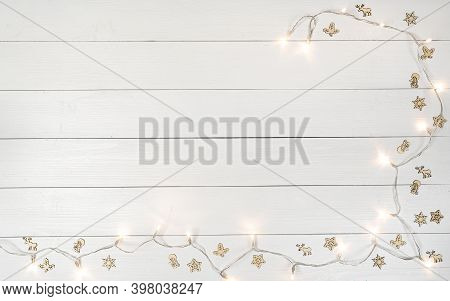 Some Small Decorative Icons And Holiday Lights On A Wooden White Background