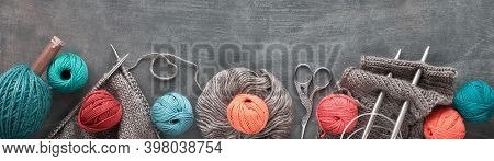 Various Wool Yarn And Knitting Needles, Creative Knitting Hobby. Panoramic Border On Dark Wood