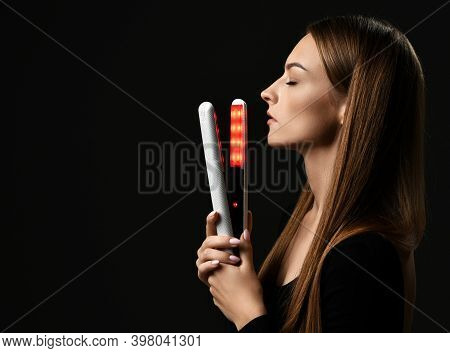Profile Of Young Pretty Woman Model With Long Straight Hair Standing Holding Hair Straightener In Ha