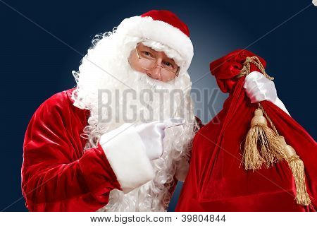 Santa Claus with his magic gift red bag full of presents poster