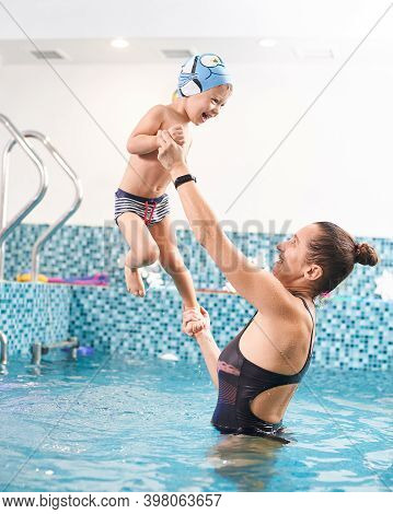 Mother Supporting Her Toddler Son In Swimming Pool Over Blue Water. Happy Kid Having Great Time With