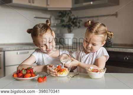 Happy Having Fun Little Siblings Girls Having Breakfast Of  With Milk And Ripe Strawberries In A Rea