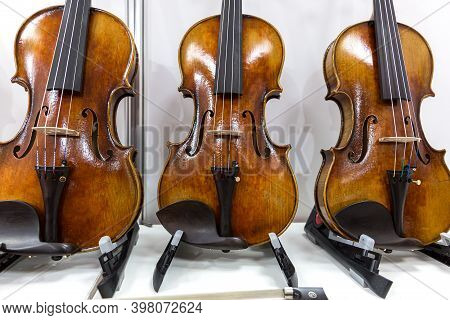 A Viola And Two Classical Violins Stand On Stands Against The Wall. Musical Instruments Of The Symph