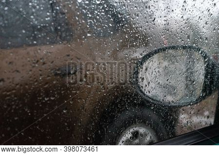 Natural Raindrops On Cars Window. Blurry Raindrops Fall On The Car Window With A Mirror In The Backg