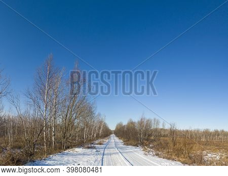 Straight Snow-covered Road In The Woods And Fields Under A Cloudless Sky