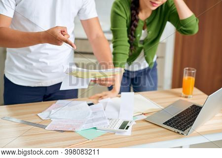 Angry Young Couple Arguing By Their Many Debts At Home. Financial Family Problems Concept.
