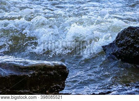 Waves Run Onto The Shore And Crash Against The Rocks, Creating Many Splashes And Splashes Near The S