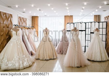 Beautiful Wedding Dresses, Bridal Dress Hanging On Hangers And Mannequins In Studio, Shop. Fashion L