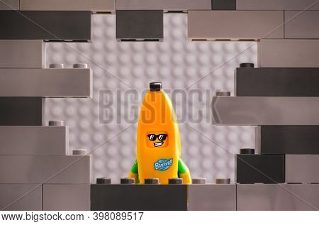 Tambov, Russian Federation - August 26, 2020 Lego Banana Guy Minifigure Looking Through A Hole In Gr