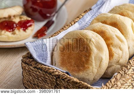 English Muffins In A Basket With A Muffin And Preserves In Background On A Wooden Table