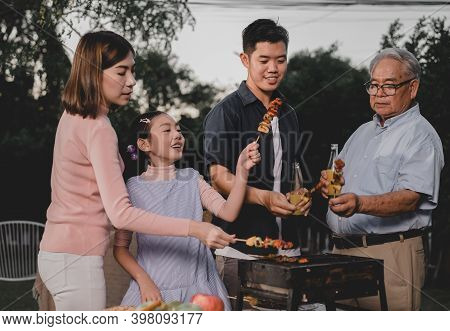 Asian Family Having A Barbecue Party At Home. Cooking Grilled Bbq For Dinner In Backyard. Lifestyle