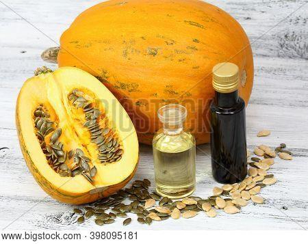 Oil Made From Pumpkin Seeds. Oil Pumpkin Cut In Half, Fresh Pumpkin Seeds Around.