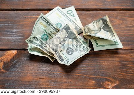 Crumpled Banknotes On A Wooden Background. Crumpled Dollars Studio Image.